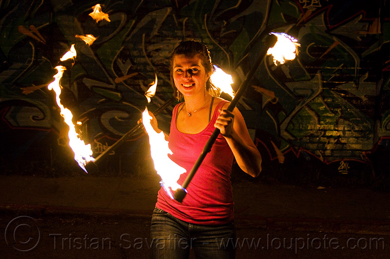 savanna spinning fire staffs, double staff, fire dancer, fire dancing, fire performer, fire spinning, fire staves, flames, graffiti, night, people, wall, woman