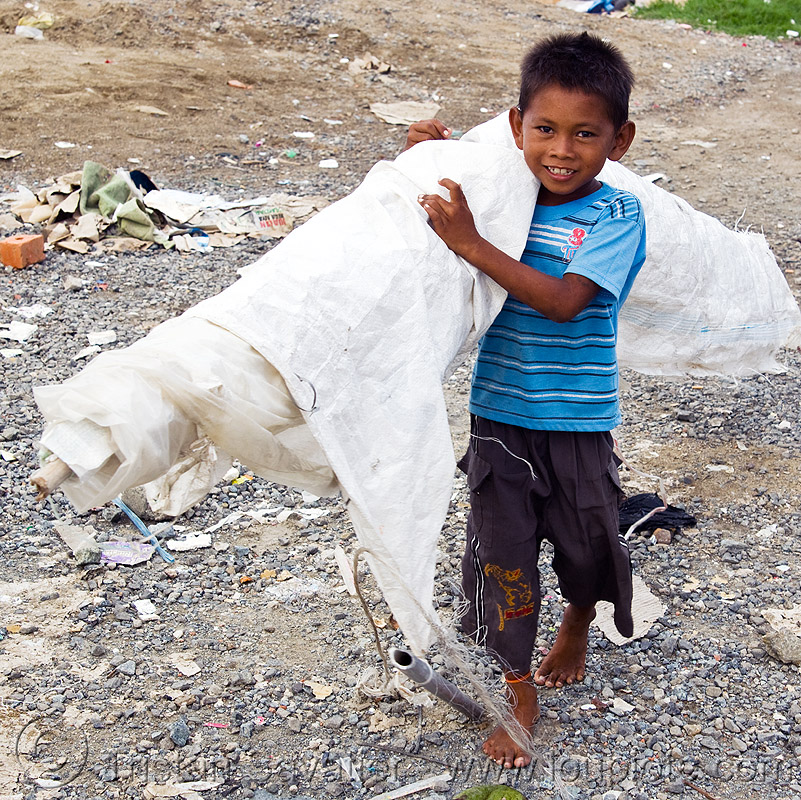 scavenger kid carrying white tarp, boy, child, garbage, homeless camp, kid, lahad datu, poor, roll, rubbish, scavenger, tarp, trash