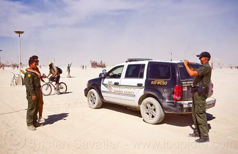 sheriff taking souvenir photo with naked man - burning man 2012, cops, jumpsuits, law enforcement, leo, officers, photographer, police uniform, sheriff, suv, tactical uniform, taking photo
