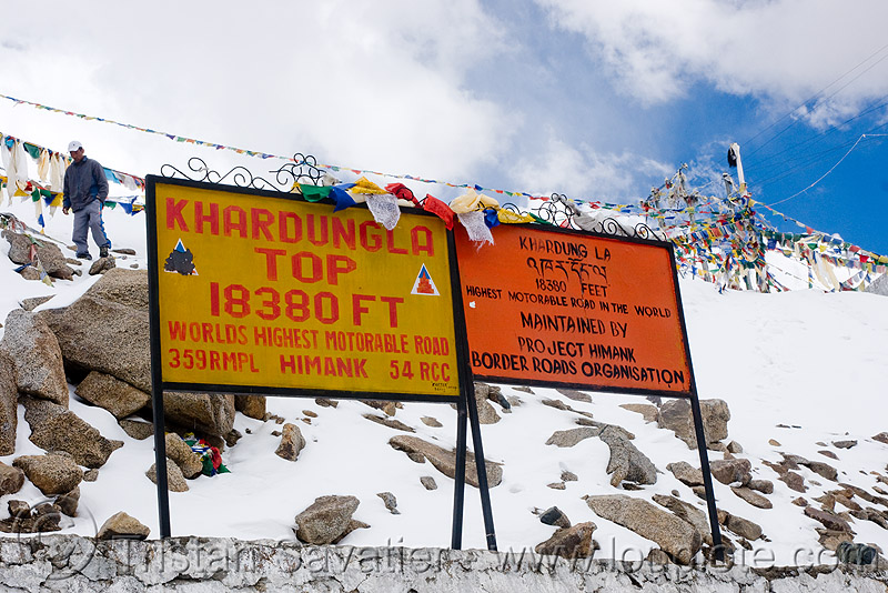 signs with incorrect (inflated) elevation - khardungla pass - ladakh (india), border roads organisation, bro, buddhism, khardung la pass, ladakh, mountain pass, mountains, prayer flags, road, signs, snow, tibetan