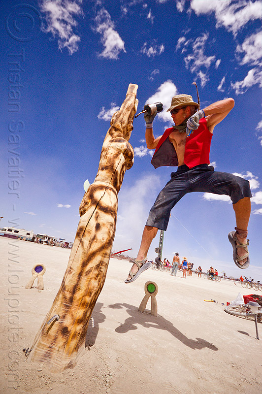 singeing a wooden sculpture - burning man 2012, argia, bruce medhurst, crystal goddess, jump, jumpshot, people, propane torch, wood