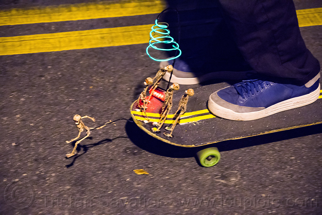 skateboard with small skeletons - dia de los muertos, day of the dead, double yellow line, el-wire, halloween, night, riding, shoes, skateboarding, street, toy skeletons