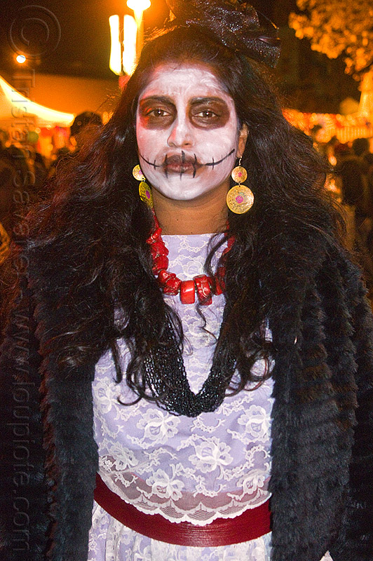 skull makeup and lace dress, day of the dead, dia de los muertos, dramatic, face painting, facepaint, halloween, lace dress, latino woman, night, red necklace, sad, skull makeup, white dress, yellow earrings