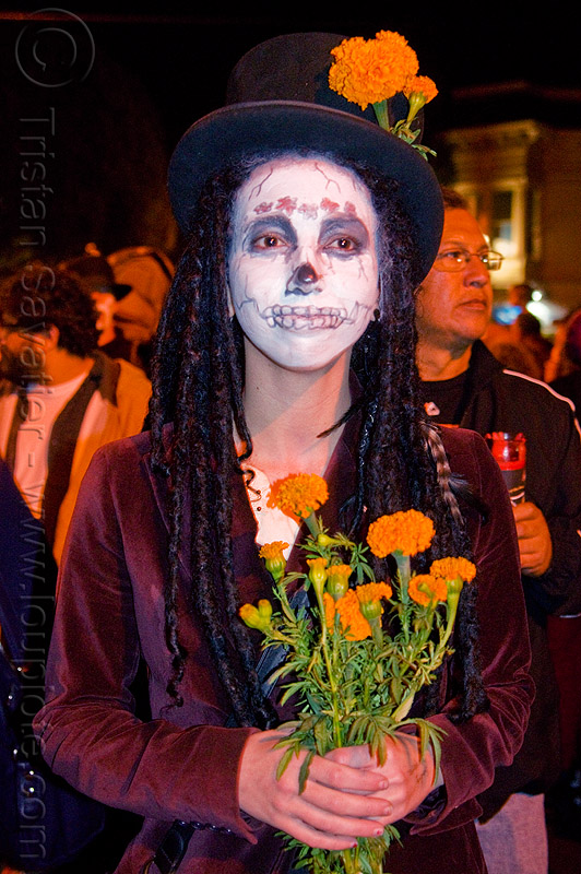 skull makeup and orange marigold flowers - tagetes, day of the dead, dia de los muertos, dreadlocks, dreads, face painting, facepaint, halloween, hat, holding flowers, night, orange flowers, orange marigold, skull makeup, tagetes, woman