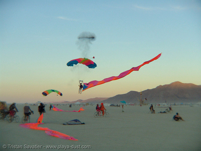 skydiver girl george landing with eel - burning-man 2005, burning man, burning sky, eels, girl george, parachute, parachutist, skydiver, skydiving, streamer flags, streamers, woman