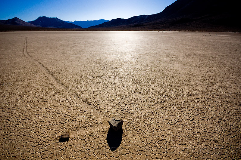 sliding rocks on the racetrack (death valley), backlight, cracked mud, crossing, death valley, desert, dry lake, dry mud, mountains, racetrack playa, sailing stones, sliding rocks, tracks