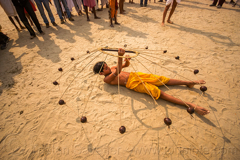 spinning balls with ropes (india), boy, game, hindu, hinduism, indian spinning balls, kumbha mela, lying down, maha kumbh mela, metal balls, performer, ropes