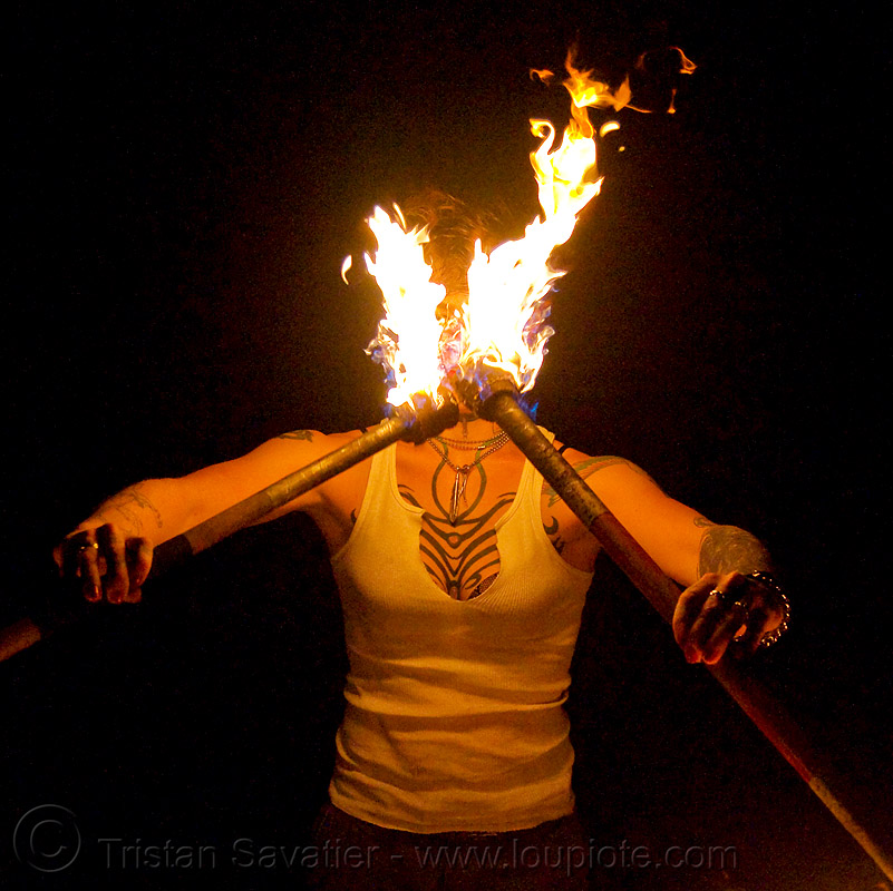 spinning fire staffs (san francisco) - fire dancer - leah, double staff, fire dancer, fire dancing, fire performer, fire spinning, fire staffs, fire staves, leah, night, spinning fire, tattooed, tattoos, woman