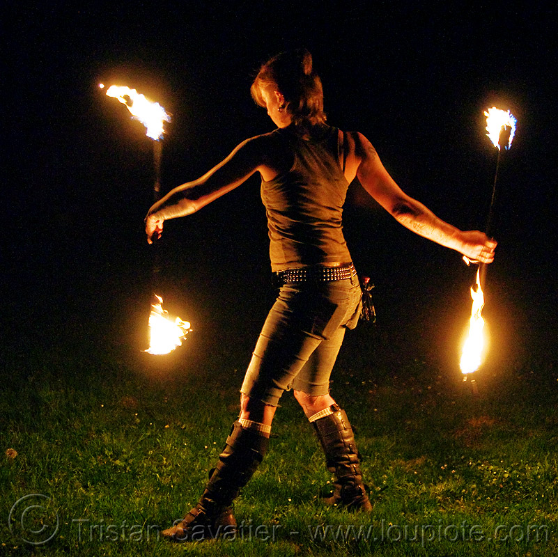 spinning fire staves on the grass - leah, backlight, boots, fire dancer, fire dancing, fire performer, fire spinning, fire staffs, fire staves, flames, grass, leah, low key, night, turf, woman