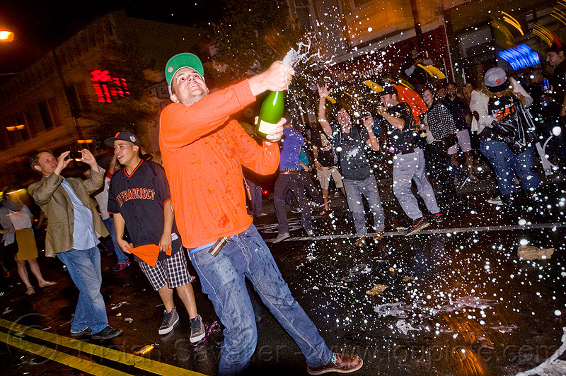 spraying champagne - SF giants fans celebrating, 2012 world series, alcohol, baseball fans, celebration, crowd, editorial, go giants, man, night, party, partying, people, sparkling wine, sports fans, street party