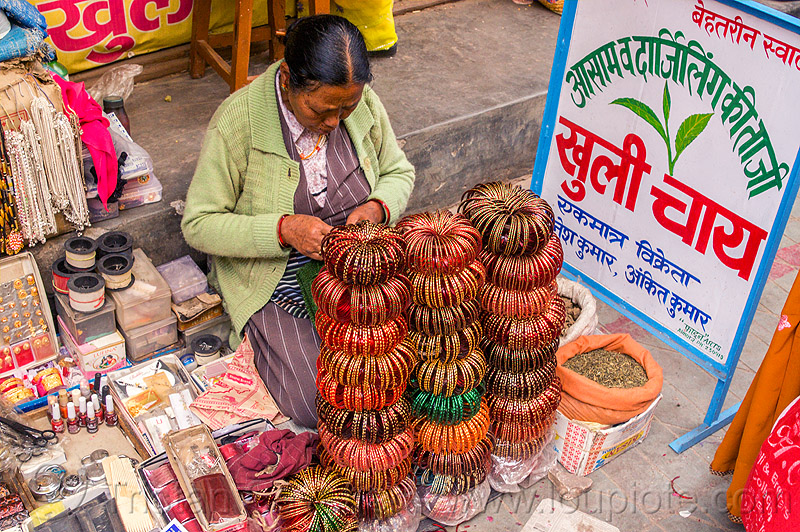 stacks of bracelets in almora street market (india), almora, bracelets, bundles, loose tea, selling, sign, sitting, stacks, stall, street market, street seller, street vendor, tea leaves, woman