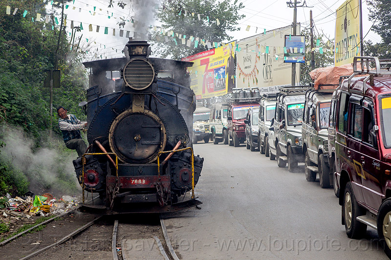 steam locomotive sharing road with cars - darjeeling (india), 788, 788 tusker, darjeeling himalayan railway, darjeeling toy train, man, narrow gauge, operator, people, railroad, railroad tracks, rails, smoke, smoking, steam engine, steam train engine, street, traffic, traffic jam, worker