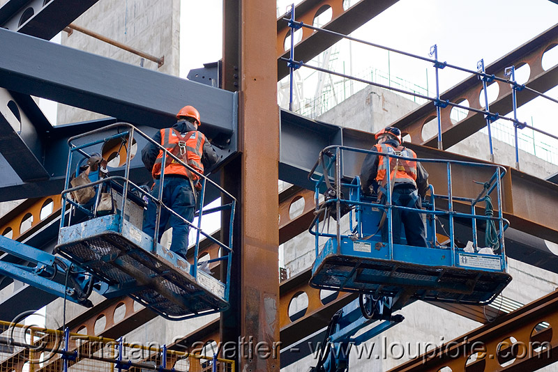 steel frame building construction - steel beams - the walbrook (london), aerial lift, boom lift, cherry picker, construction worker, crane, helmet, high-visibility jacket, high-visibility vest, hydraulic, people, reflective, reflective jacket, reflective vest, safety harness, safety helmet, workers, working