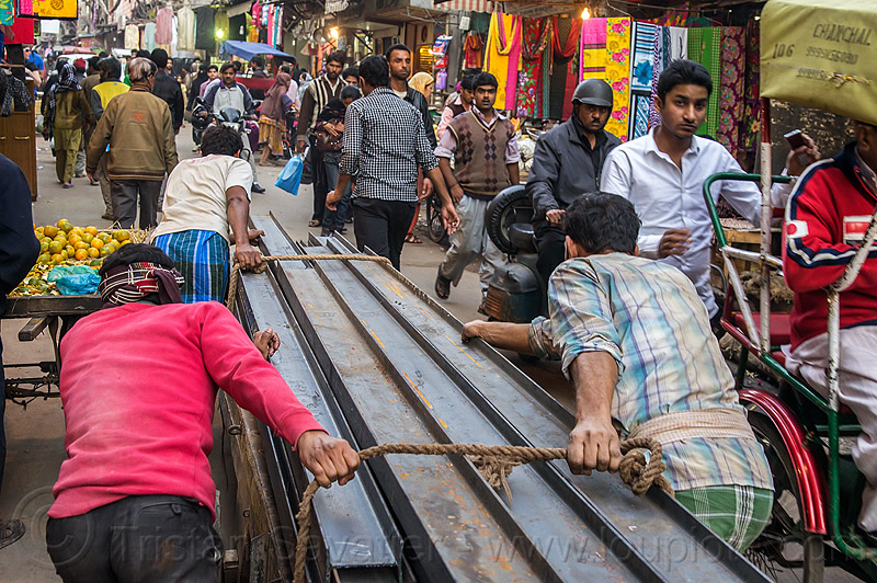 steel I-beam rails rolled on cart in street (india), construction, crowd, delhi, i-beams, market, men, pushing, rope, roped, steel beams, street, workers, working