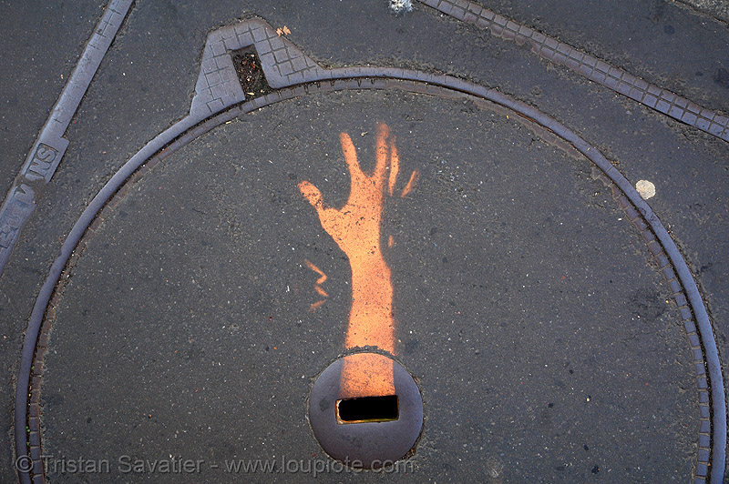 stencil graffiti on manhole cover - hand (paris, france), arm, graffiti, hand, help!, manhole cover, paris, plaque d'egout, plaque d'égout, regard de chaussée, stencil, street art, tampon de regard