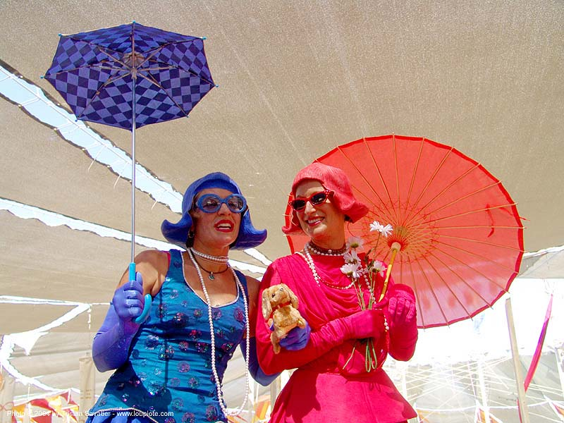 stiltwalkers with umbrellas - burning-man 2004, art, blue, burning man, center camp, costumes, girls, red, stiltwalkers, two, umbrellas, women