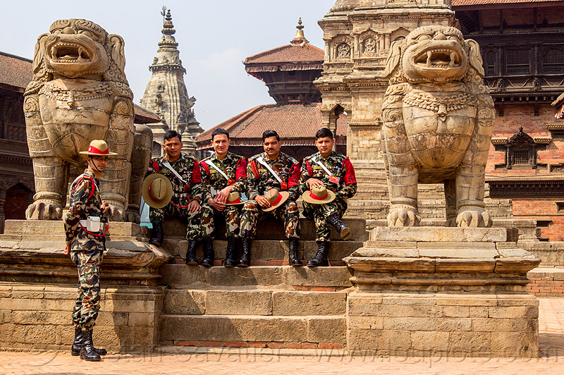 stone lions and nepali army soldiers on steps - bhaktapur durbar square (nepal), fatigues, gorkhas, guards, gurkha army, gurkha regiment, gurkhas, hat, hindu temple, hinduism, men, military, nepalese army, people, red stripe, sculptures, stairs, statue, uniform
