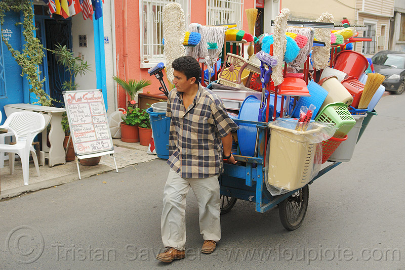 street vendor pulling cart with plastic houseware, basin, buckets, jars, man, market, mops, pastic houseware, people