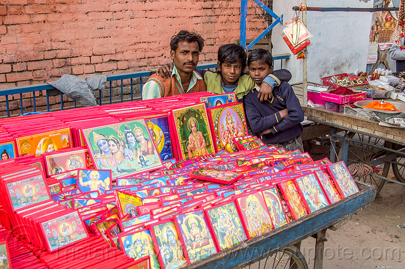 street vendor selling images of hindu gods, boys, children, daraganj, deities, father, gods, hindu, hinduism, holy images, kids, kumbha mela, maha kumbh mela, man, merchant, religion, religious, selling, shop, sons, stall, street market, vending, vendor