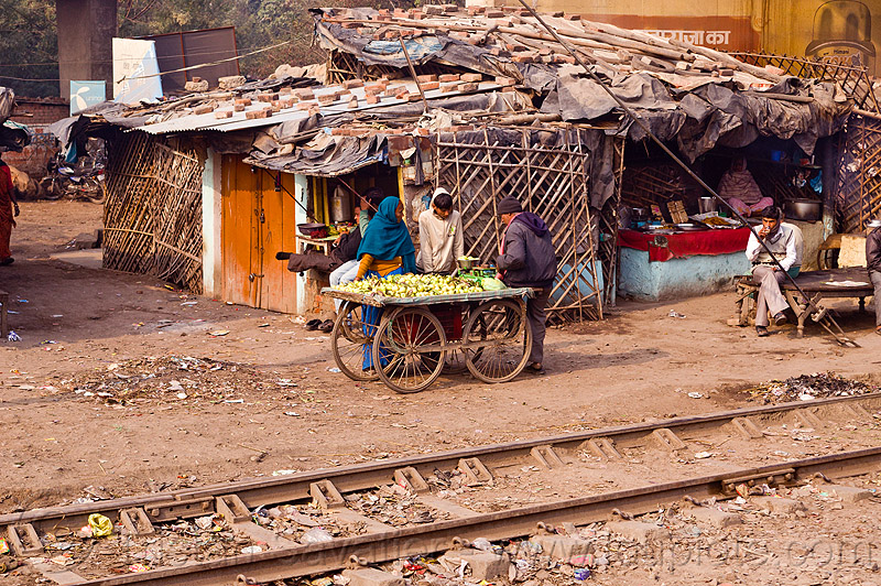 street vendor - shop along train tracks, cart, fruit cart, fruits, house, market, people, railroad, railroad tracks, rails, railway, selling, shanty house, shopping, single story house, store, village
