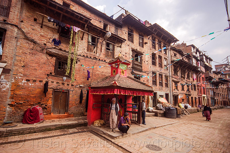 street with old brick houses and small red hindu shrine - bhaktapur (nepal), hinduism, people
