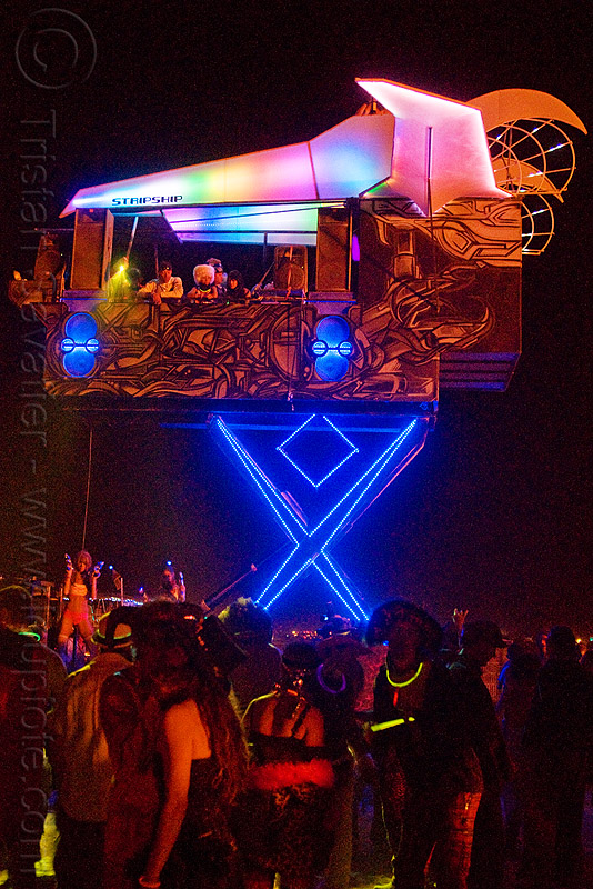 stripship art car, burning man, glowing, neons, night, people, unidentified art, unidentified art car