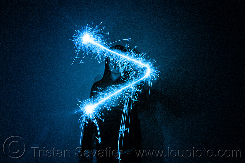 superior sign - light painting with a blue sparkler, blue, dark, greater than, icon, light drawing, light painting, sarah, shadow, silhouette, sparklers, sparkles, superior sign, symbol