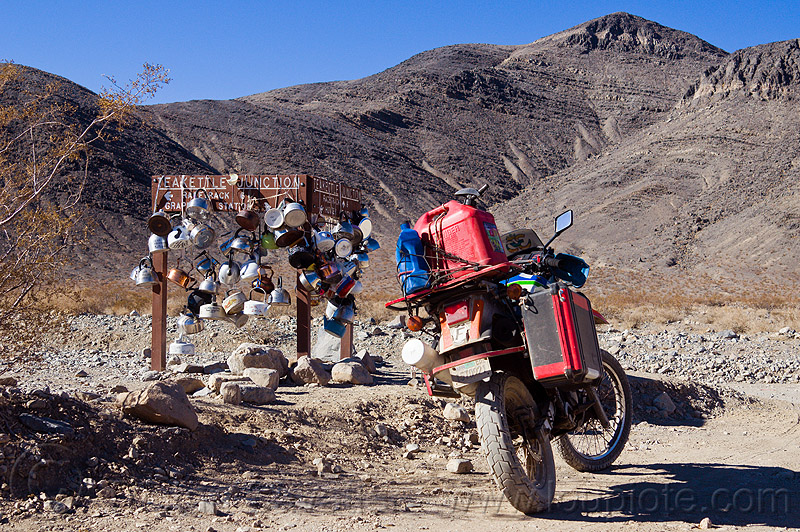teakettle junction on the road to the racetrack (death valley), death valley, desert, dirt road, dual-sport, fuel, gas can, gasoline, jerrycan, kawasaki, klr 650, motorbike touring, motorcycle touring, mountains, pannier case, petrol, plastic can, racetrack playa, rack, road sign, teakettle junction, teakettles, traffic sign, unpaved