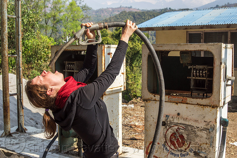 thirsty woman drinks at the petrol pump (nepal), abandoned, anne-laure, bending backward, broken, drinking, gas pump, gas station, hose, nozzle, people, petrol station