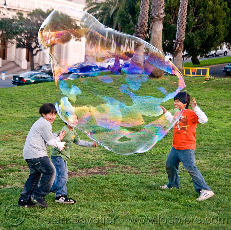 three kids playing with giant soap bubble, big bubble, children, giant bubble, iridescent, kids, lawn, park, playing, soap bubbles