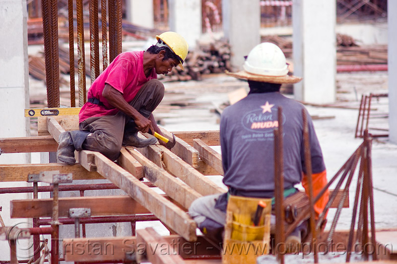 timber formwork construction - shoring, building construction, concrete forms, concrete wall forms, construction site, construction workers, hammer, lumber, man, miri, people, rebars, safety helmet, scaffolding, sitting, working
