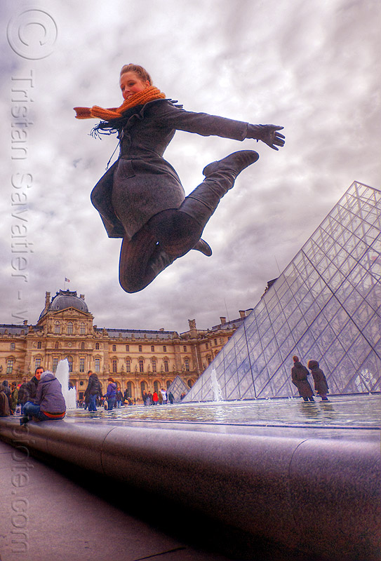 tourist near the glass pyramid at le louvre museum (paris), clouds, crowd, fountain, jump shot, le louvre, museum, paris, pyramid, scarf, sophie, tourists, water, woman