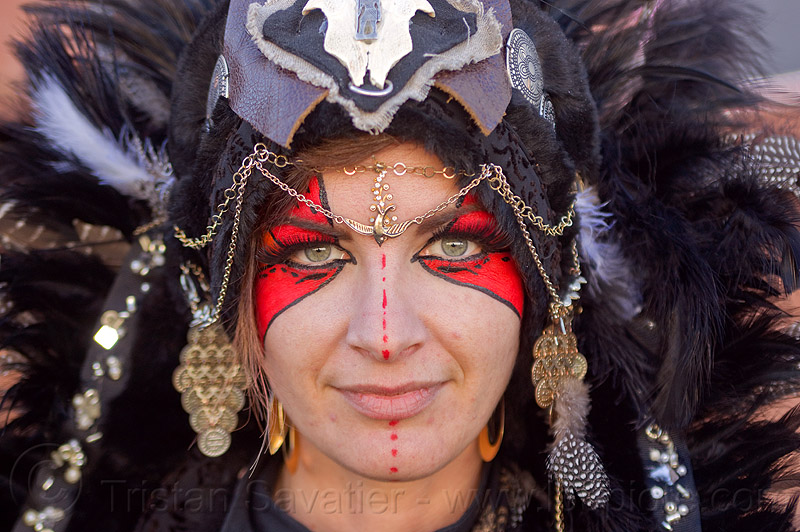 tribal headdress - chain jewelry - red face paint, burning man decompression, chains, earrings, eye makeup, face jewelry, facepaint, feather, headdress, leather, tribal fashion, woman