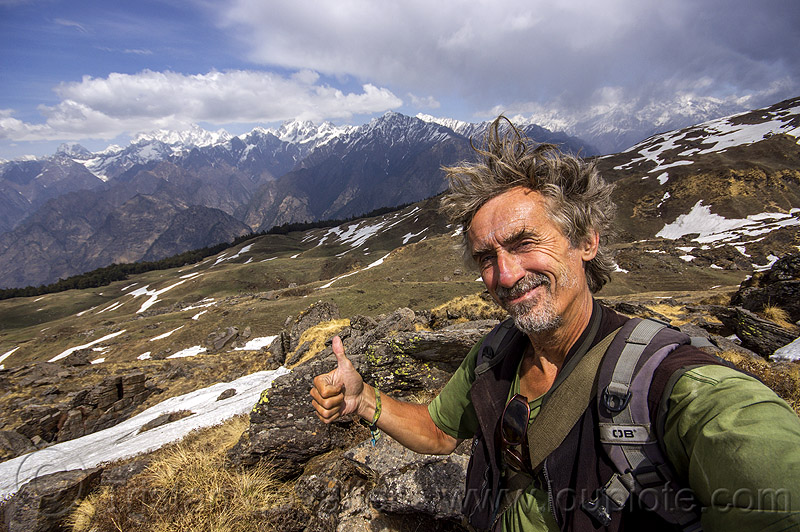 tristan savatier - hiking in the indian himalaya mountains near joshimath (india), cloudy, hiking, india, man, mountains, pastures, rocks, self-portrait, selfie, snow patches, thumb up, trekking, windy