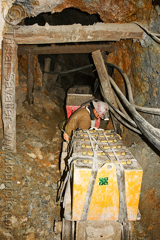 trolley carrying ore out of the mine, adit, batteries, beams, cerro rico, electric, man, mina candelaria, mine worker, miner, mining, pipes, potosí, rails, safety helmet, trolley, tunnel, wood