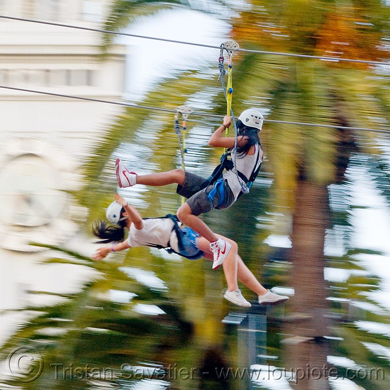 two girls riding the zip-line over san francisco, adventure, cable line, cables, campanil, climbing helmet, clock tower, embarcadero, embarcadero tower, extreme sport, fast, ferry building, gear, hanging, harness, justin herman plaza, mountaineering, moving, moving fast, palm trees, people, speed, steel cable, trolley, tyrolienne, urban, woman, zip line, zip wire, ziptrek