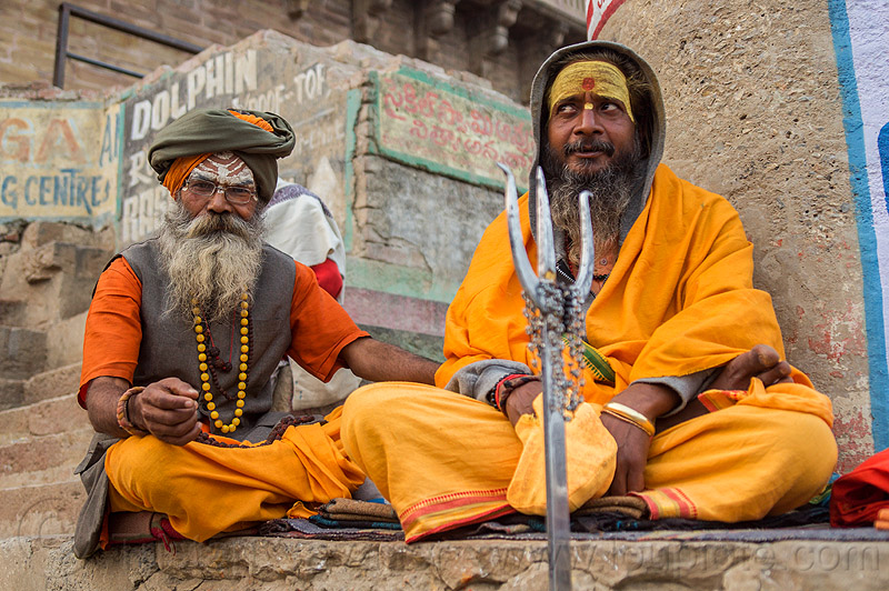 two sadhus with trident on the ghats of varanasi - hindu holy men (india), babas, beard, bhagwa, cross-legged, ghats, headdress, hindu, hinduism, india, men, sadhus, saffron color, sitting, tilak, trident, turban, varanasi
