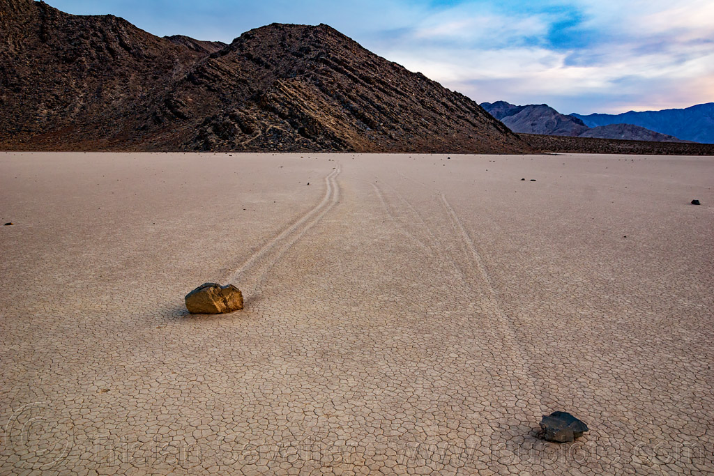 two sailing stones on the racetrack playa - death valley, cracked mud, death valley, dry lake, dry mud, mountains, racetrack playa, sailing stones, sliding rocks