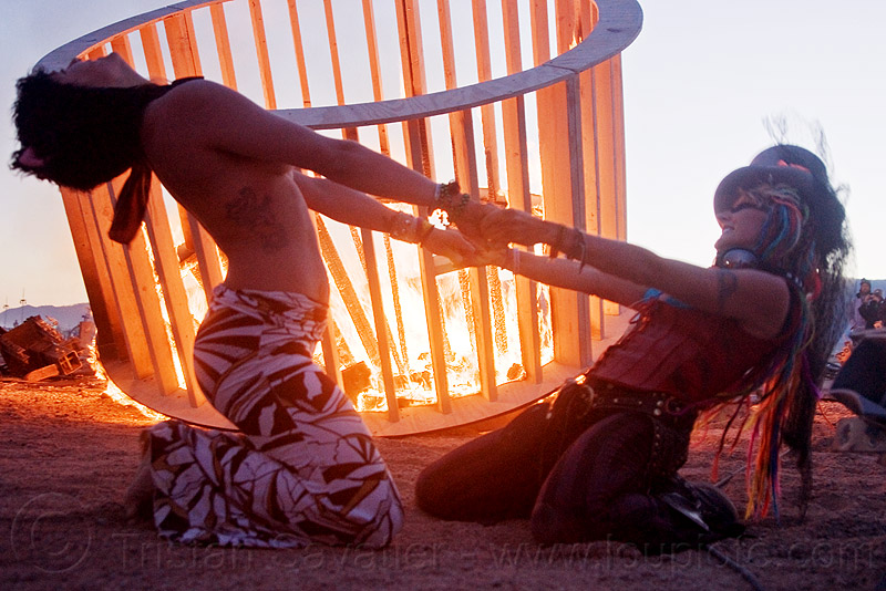 two women dancing - cylindrical wooden frame burning, burning, cylinder, cylindrical, dancing, dusk, fire, flames, frame, heather, stretching, woman, wood, wooden