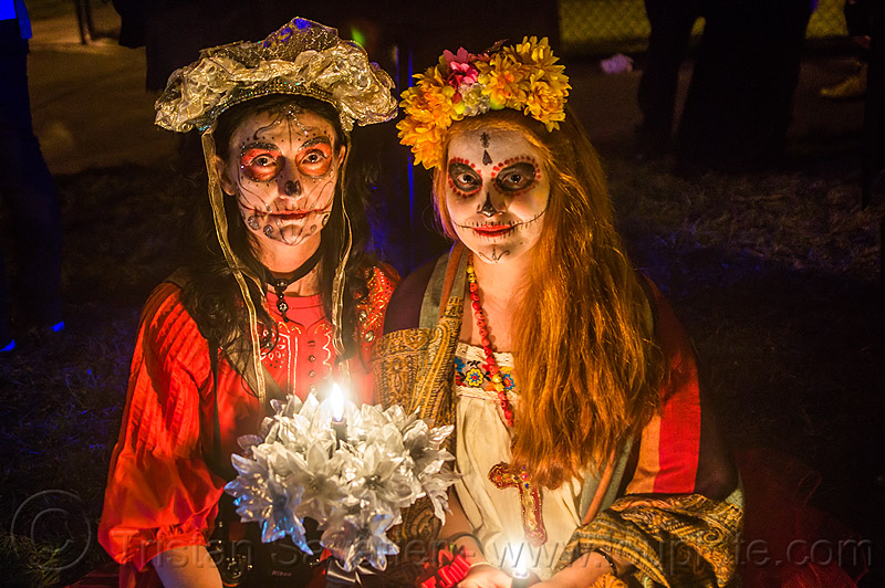 two women with sugar skull makeup - dia de los muertos (san francisco), candle, day of the dead, dia de los muertos, face painting, facepaint, flower headdress, halloween, night, sugar skull makeup, white flowers, women