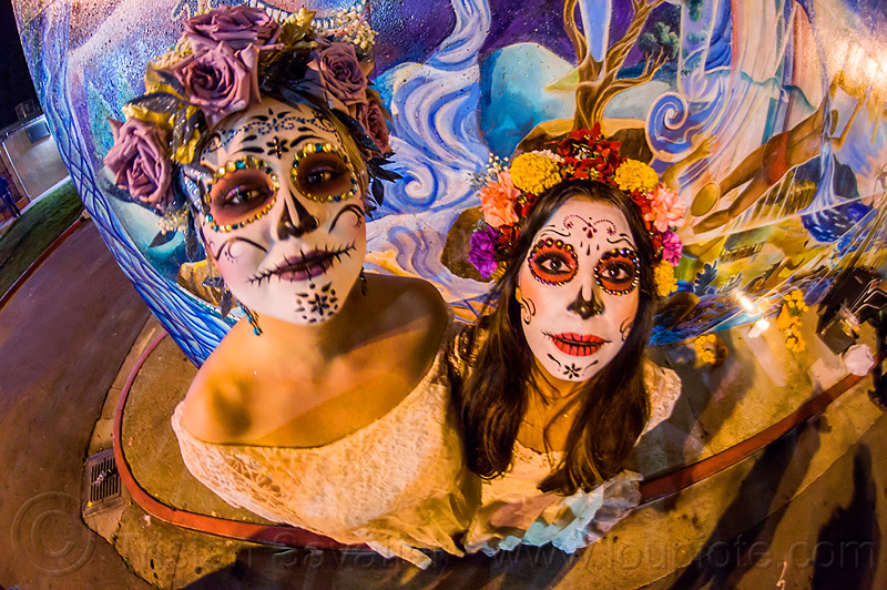 two women with white sugar skull makeup and flower headdresses, andrea, bindis, day of the dead, dia de los muertos, face painting, facepaint, flower headdress, flowers, halloween, mariana, mural, night, sugar skull makeup, wall, women