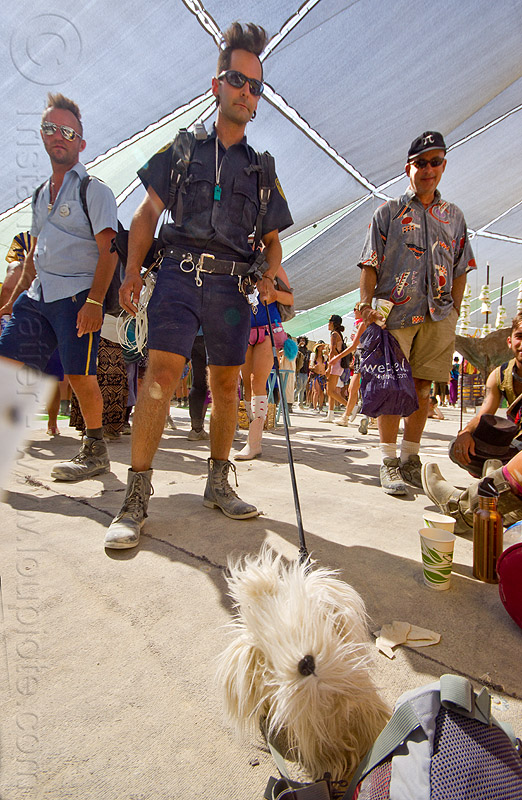 U.S. customs and border patrol officer with drug sniffing dog - burning man 2013, bag, cop, costume, detection dog, law enforcement officer, leash, leo, people, performance, police, police uniform, poodle, shorts, sniffer dog, sunglasses, u.s. customs and border protection