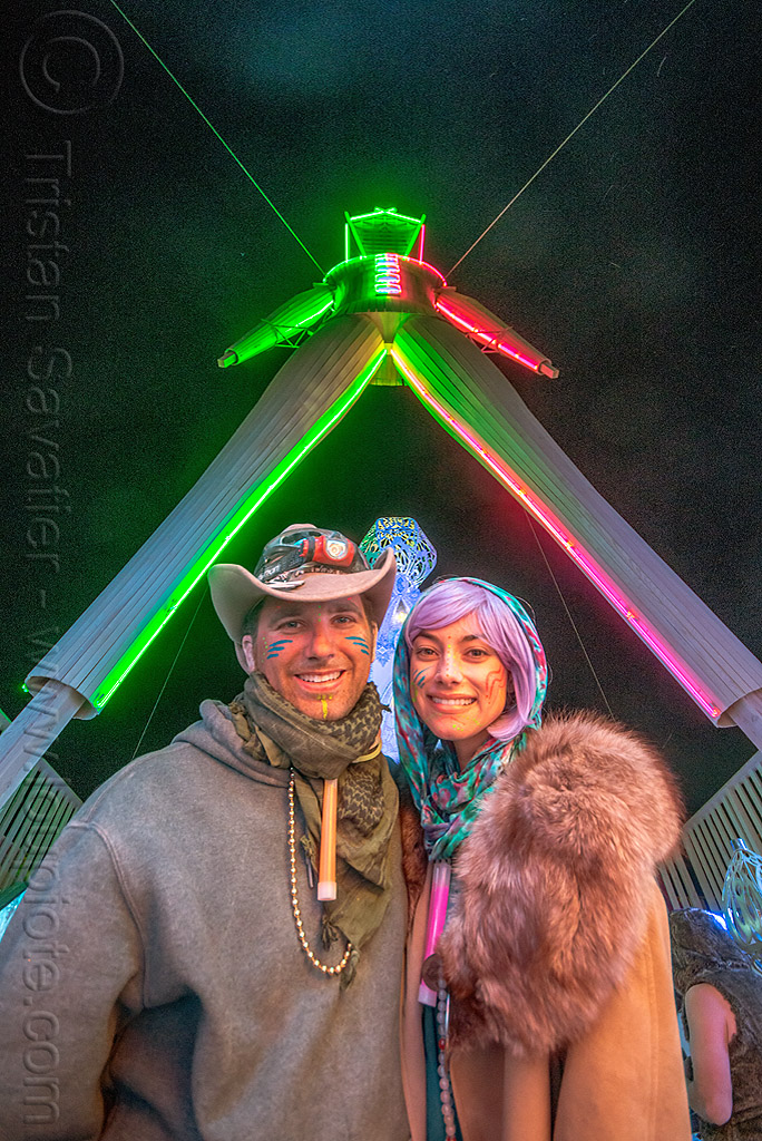 under the man at night - burning man 2015, britt, burning man, couple, fur coat, glowing, hat, headlight, neon, night, purple wig, scarf, the man, woman