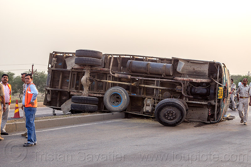 underbelly of truck overturned on median (india), crash, india, lorry, median, men, overturned, road, rollover, tata motors, traffic accident, truck accident, underbelly, wreck
