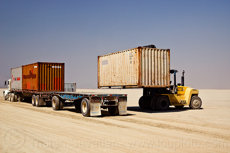 unloading containers from semi truck trailer - burning man 2012, articulated lorry, big rig, flat bed, forklift, heavy equipment, hydraulic, machinery, semi trailer, tractor-trailer, trucks