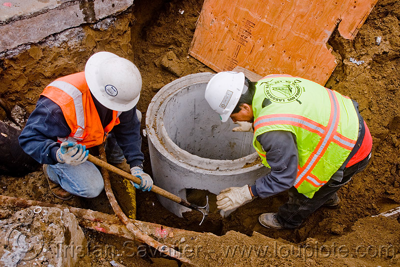 utility workers digging around storm drain construction, comcrete, construction workers, drainage, high-visibility jacket, high-visibility vest, reflective jacket, reflective vest, safety helmet, safety jacket, storm drain, utility workers, working