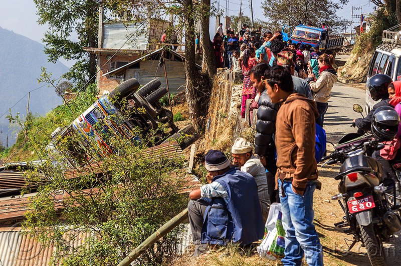villagers looking at overturned truck in ditch (nepal), crash, ditch, lorry, motorcycle, mountain road, overturned, rollover, tata motors, traffic accident, truck accident, up-side-down, wreck