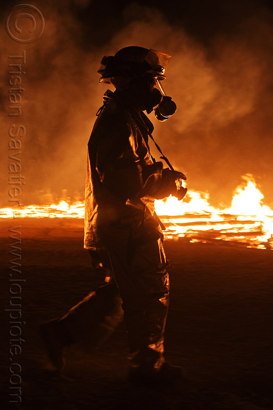 volunteer firefighter in fire-protection suit - burning man 2010, backlight, burning man, dust mask, fire suit, fire-protection suit, firefighter, night of the burn, respirator, safety helmet, smoke mask