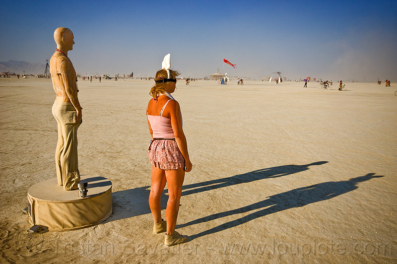 watching the horizon - burning man 2013, art installation, bunny ears, burning man, horizon, playa, sculpture, shadows, standing, statue, unidentified art, woman