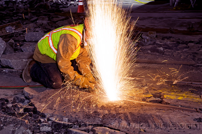 welder cutting a rail with an oxy-acetylene torch, demolition, high-visibility jacket, high-visibility vest, light rail, man, muni, night, ntk, oxy-acetylene cutting torch, oxy-fuel cutting, railroad construction, railroad tracks, rails, railway tracks, reflective jacket, reflective vest, safety helmet, safety vest, san francisco municipal railway, sparks, track maintenance, track work, welder, welding, worker, working